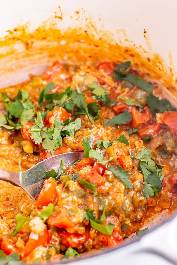 White pot of menemen with a spoon and topped with coriander