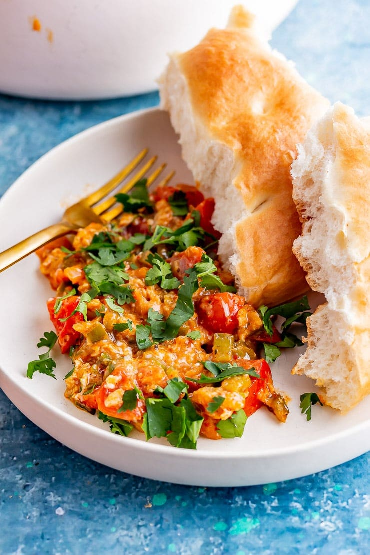 White bowl of menemen with a gold fork and bread on a blue background
