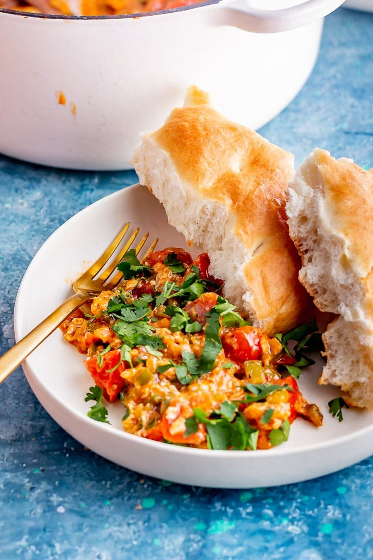 White bowl of menemen with bread and a gold fork on a blue bowl