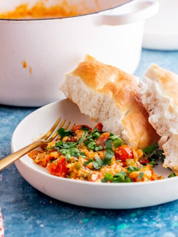 Side on shot of menemen with bread in a white bowl on a blue background