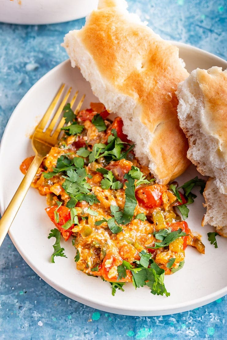 White bowl of menemen with bread and a gold fork