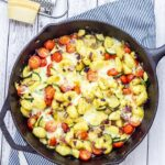 Overhead shot of summer gnocchi skillet on a white wooden background