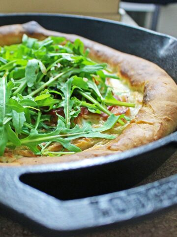 This simple skillet pizza makes perfect use of your cast iron skillet & combines salty prosciutto with creamy mozzarella & garlic oil for a delicious dinner.