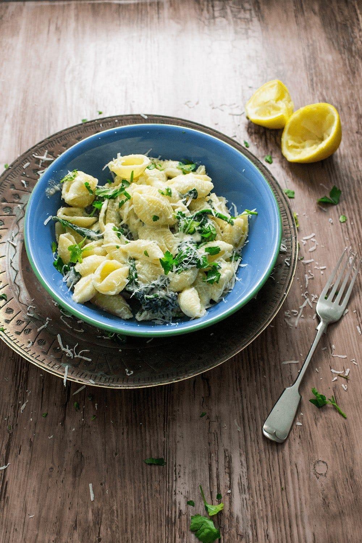 Blue bowl of lemon garlic sour cream pasta on a wooden background