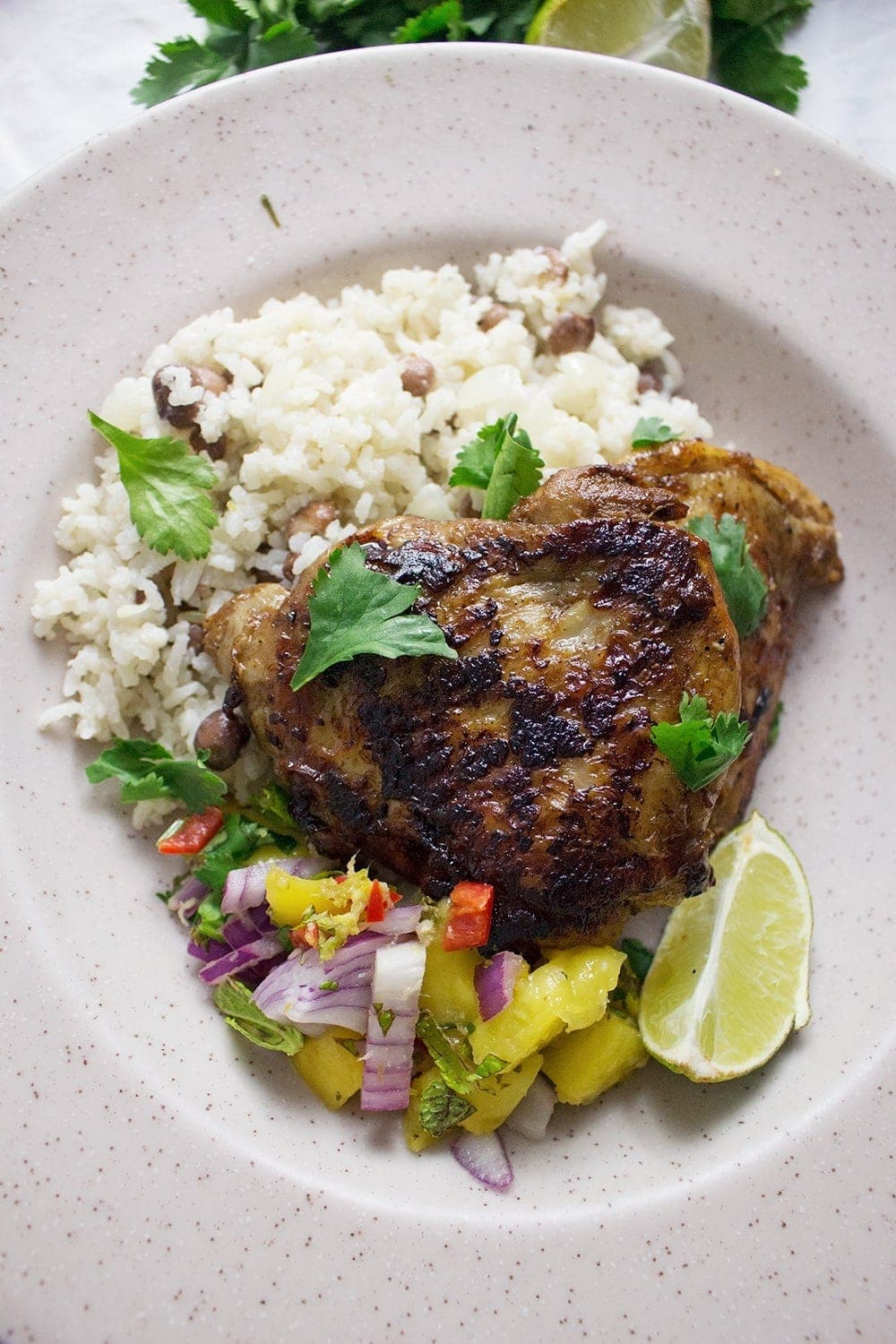 This jerk chicken is sweet and spicy, it tastes amazing served with a mango salsa and turmeric roti. Rice & peas is the perfect base for all this deliciousness!