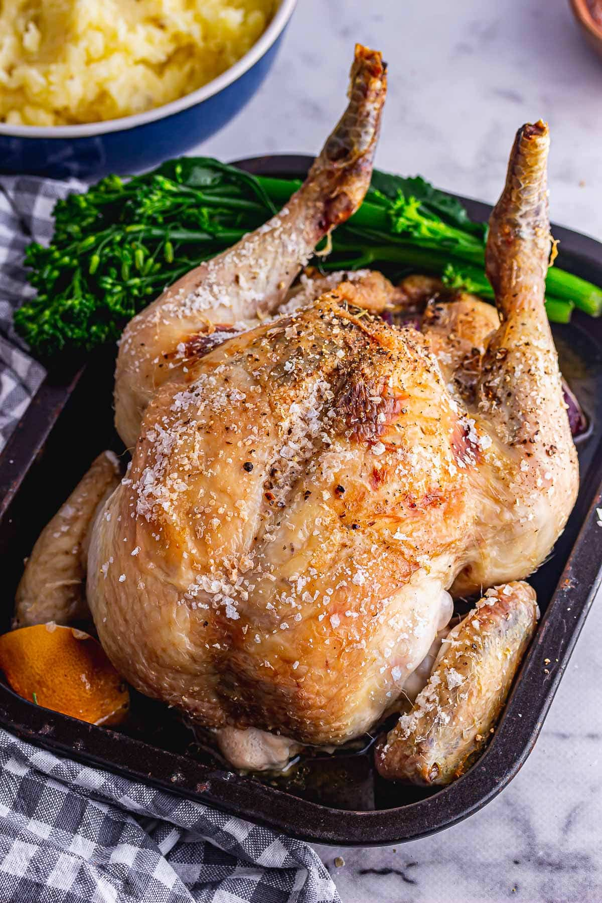 Simple whole roasted chicken with broccoli in a black roasting tin