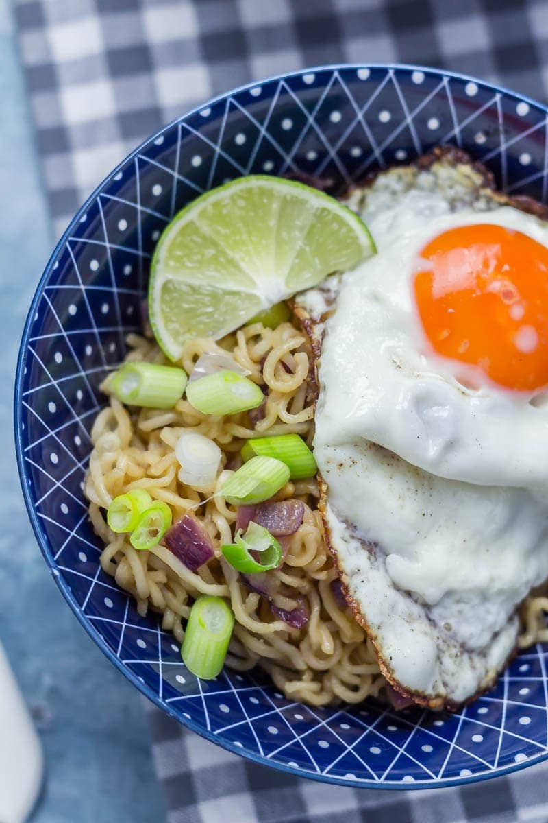 Close up of soy peanut noodles with a fried egg and lime