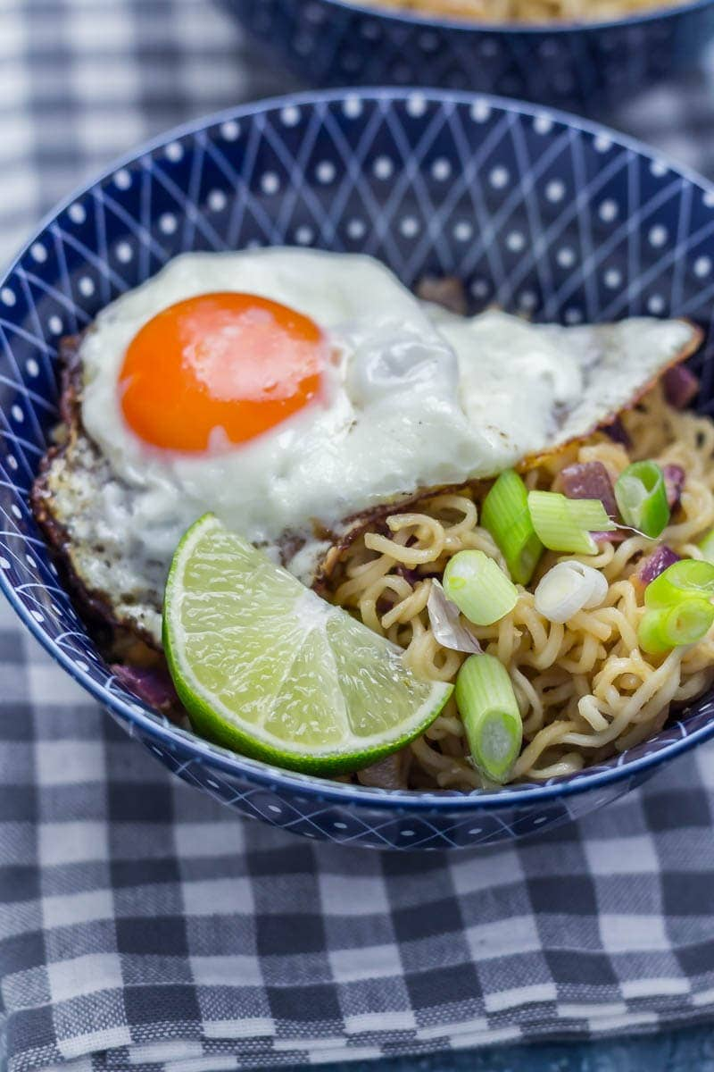 Egg and lime on a soy peanut noodles in a blue bowl