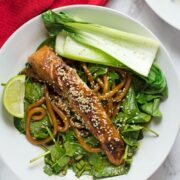 Teriyaki salmon on spinach in a white bowl