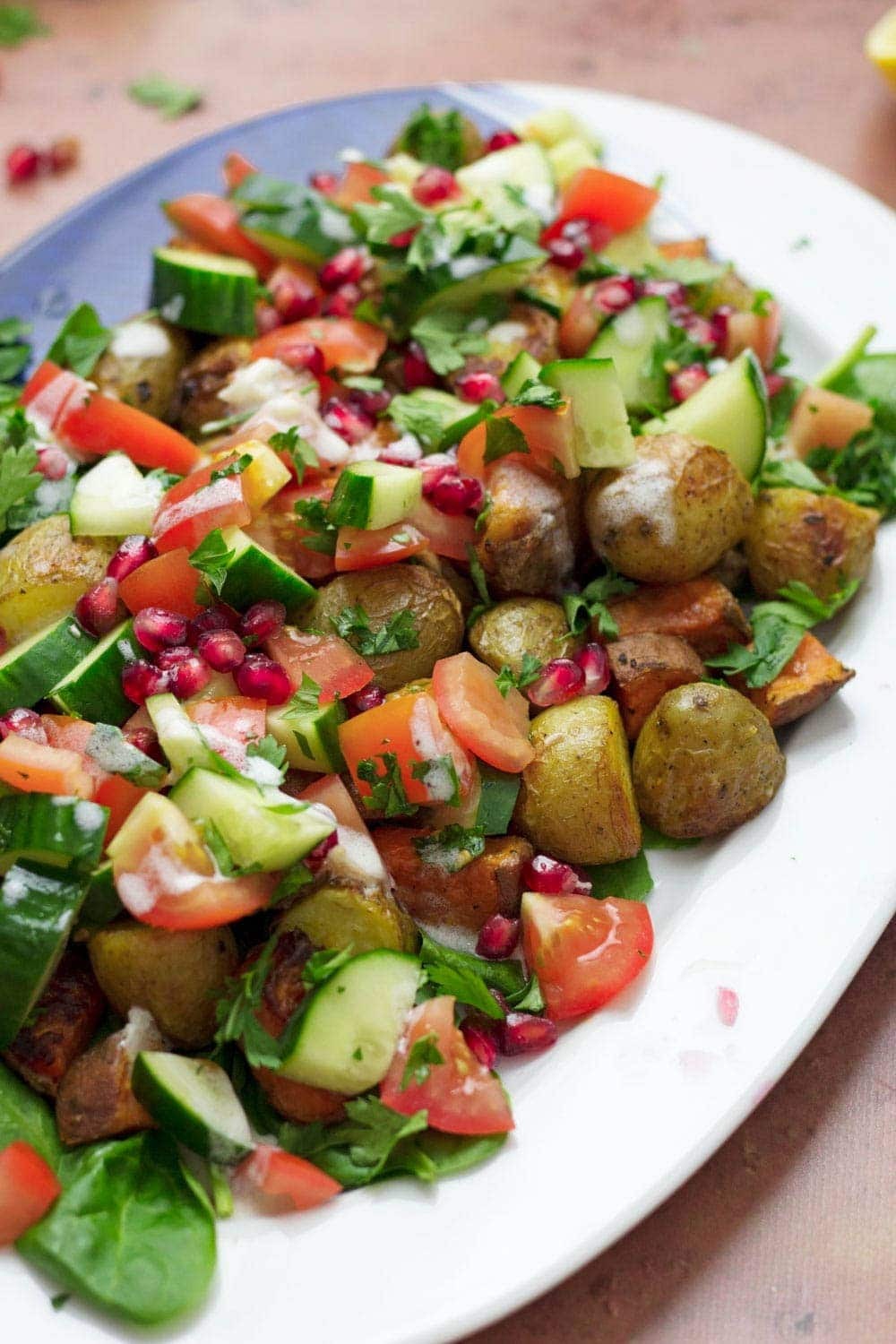 Roast potato salad with cucumber, tomatoes and pomegranate on a white dish