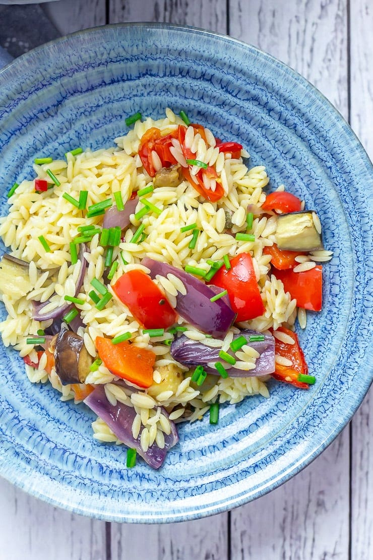 Summer orzo salad in a blue bowl on a white wooden background