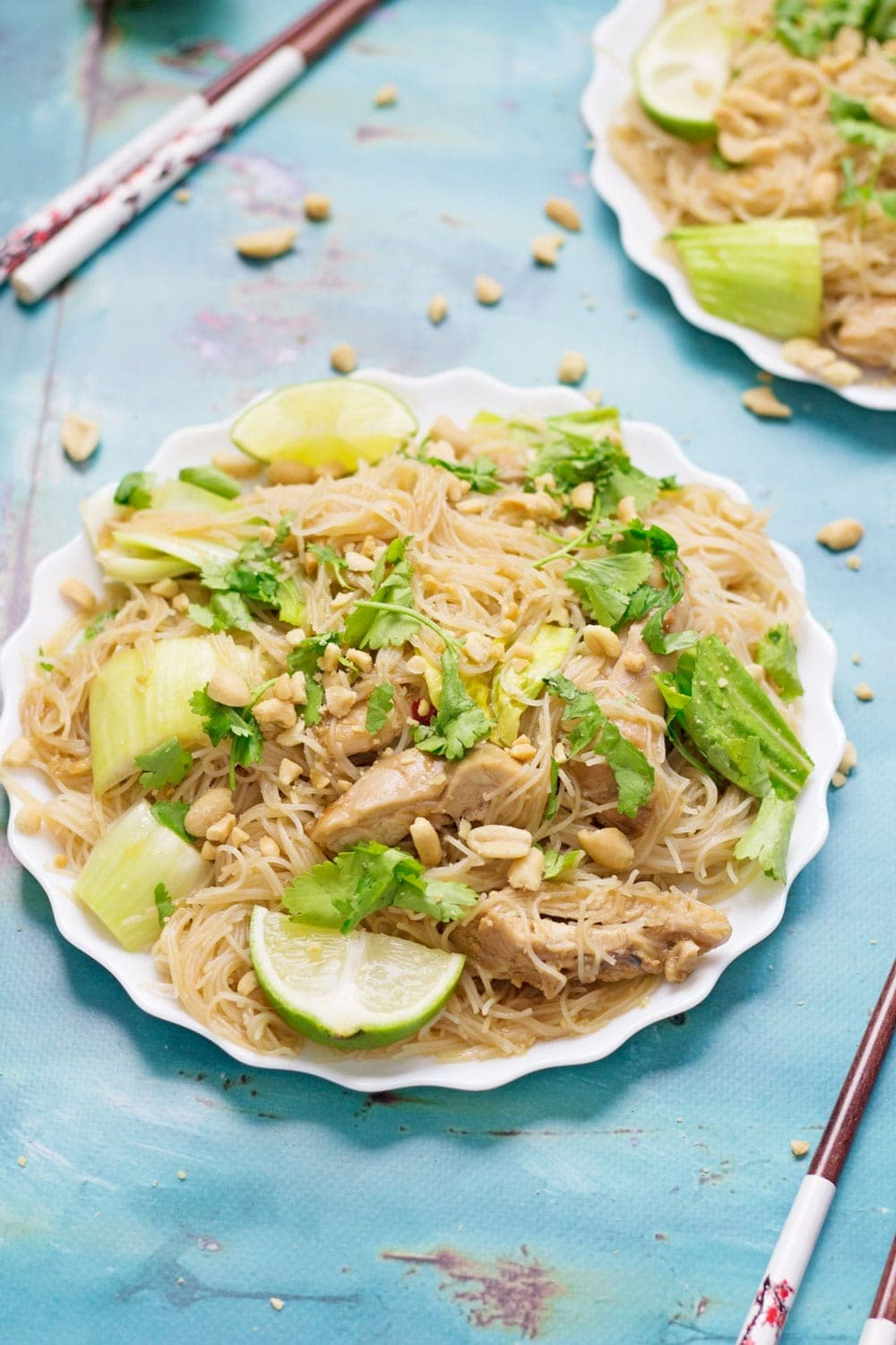 Thai chicken noodles on a white plate on a blue background