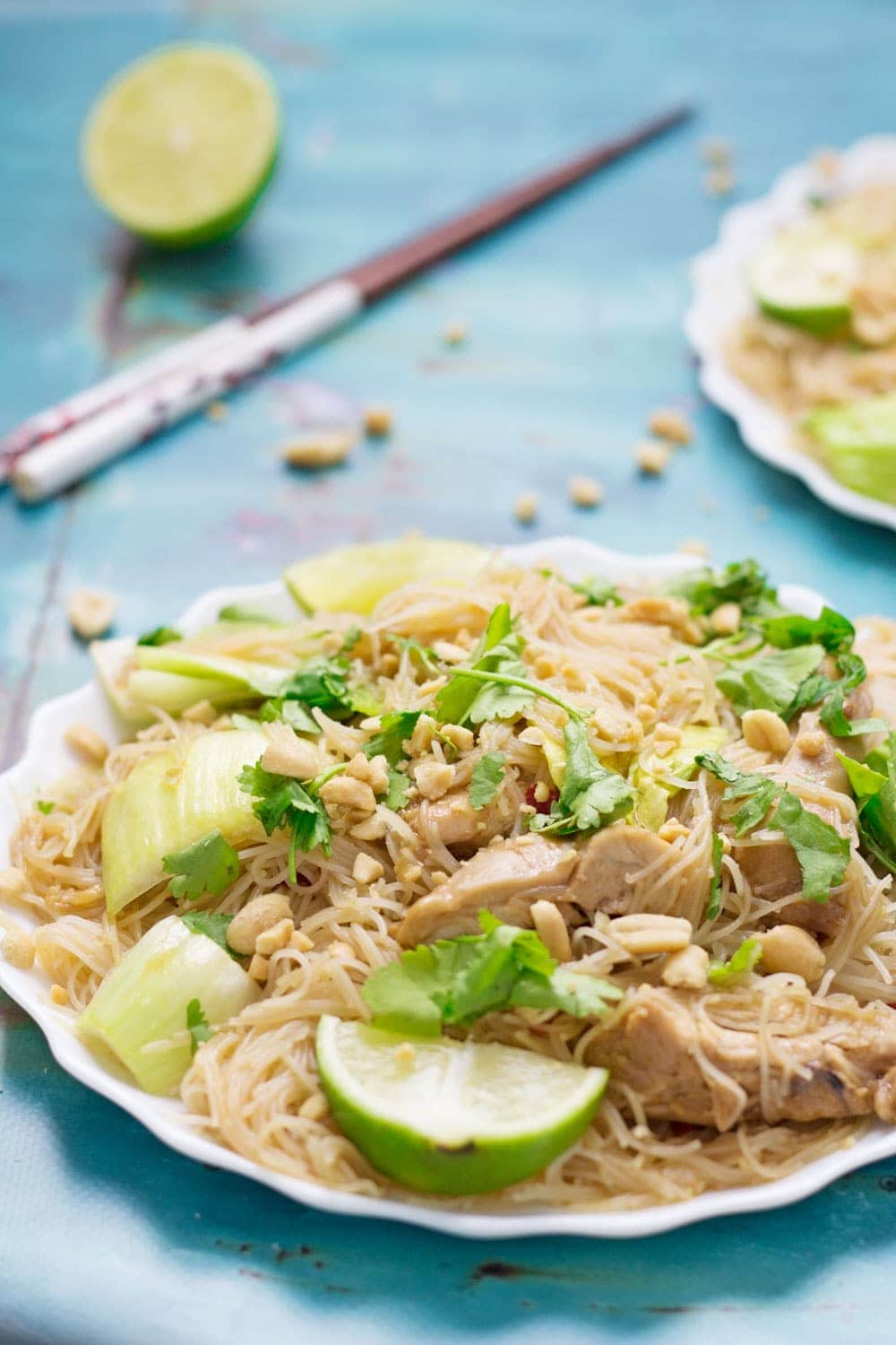 Close up of chicken noodles with lime on a white plate