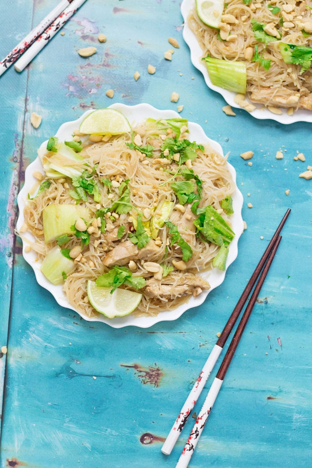 Overhead shot of white plate of chicken noodles on a blue background