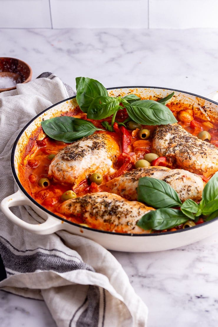 White skillet on a marble background with Italian chicken and basil