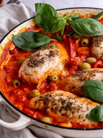 White skillet of Italian chicken with basil