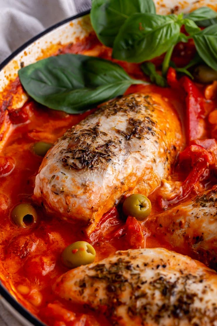 Close up of chicken in a creamy Italian sauce with olives and basil