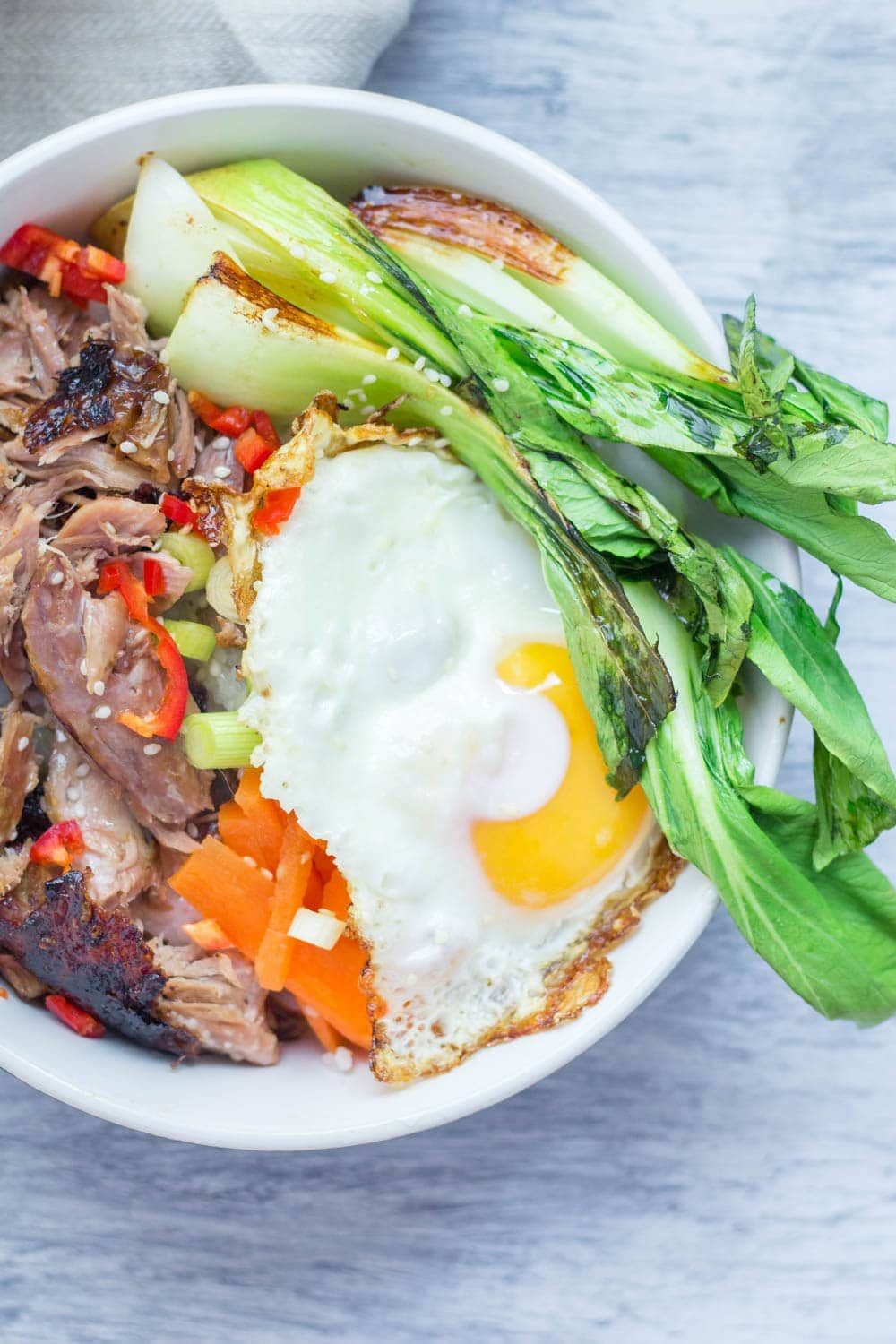 Japanese roast duck legs are shredded and served over sticky rice with pak choi, chilli and perfectly soft fried egg for a tasty dinner all in one bowl!