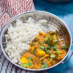 Bowl of turkey and potato curry on a blue background