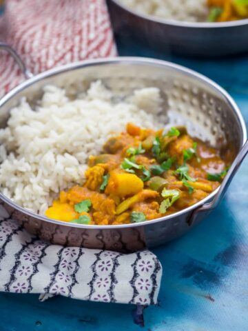 Bowl of pressure cooker turkey and potato curry on a blue background with a patterned cloth