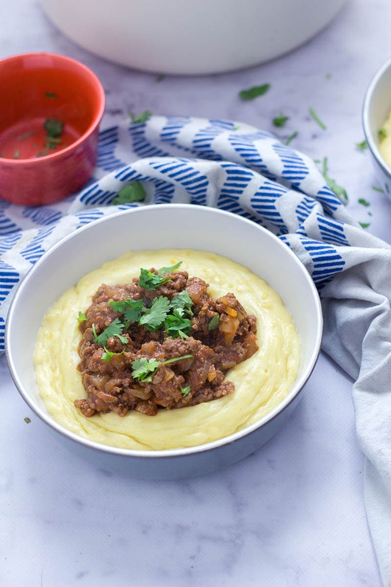Five Ingredient Beef Ragu with Creamy Polenta. This beef ragu is the perfect quick, weeknight dinner. It takes only five ingredients to make and tastes amazing served over creamy, cheesy polenta. There's no better winter meal! #beefragu #polenta #recipe #dinner