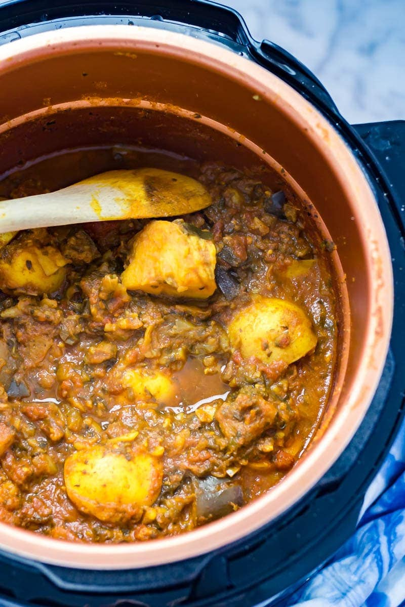 Pressure cooker curry with potato in a bronze coloured insert