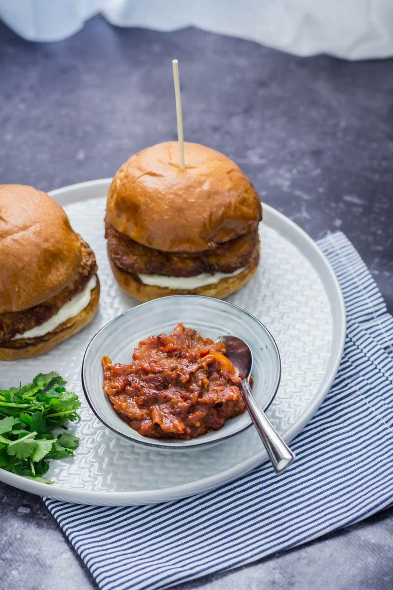 Panko halloumi sandwiches on a grey plate over a striped cloth