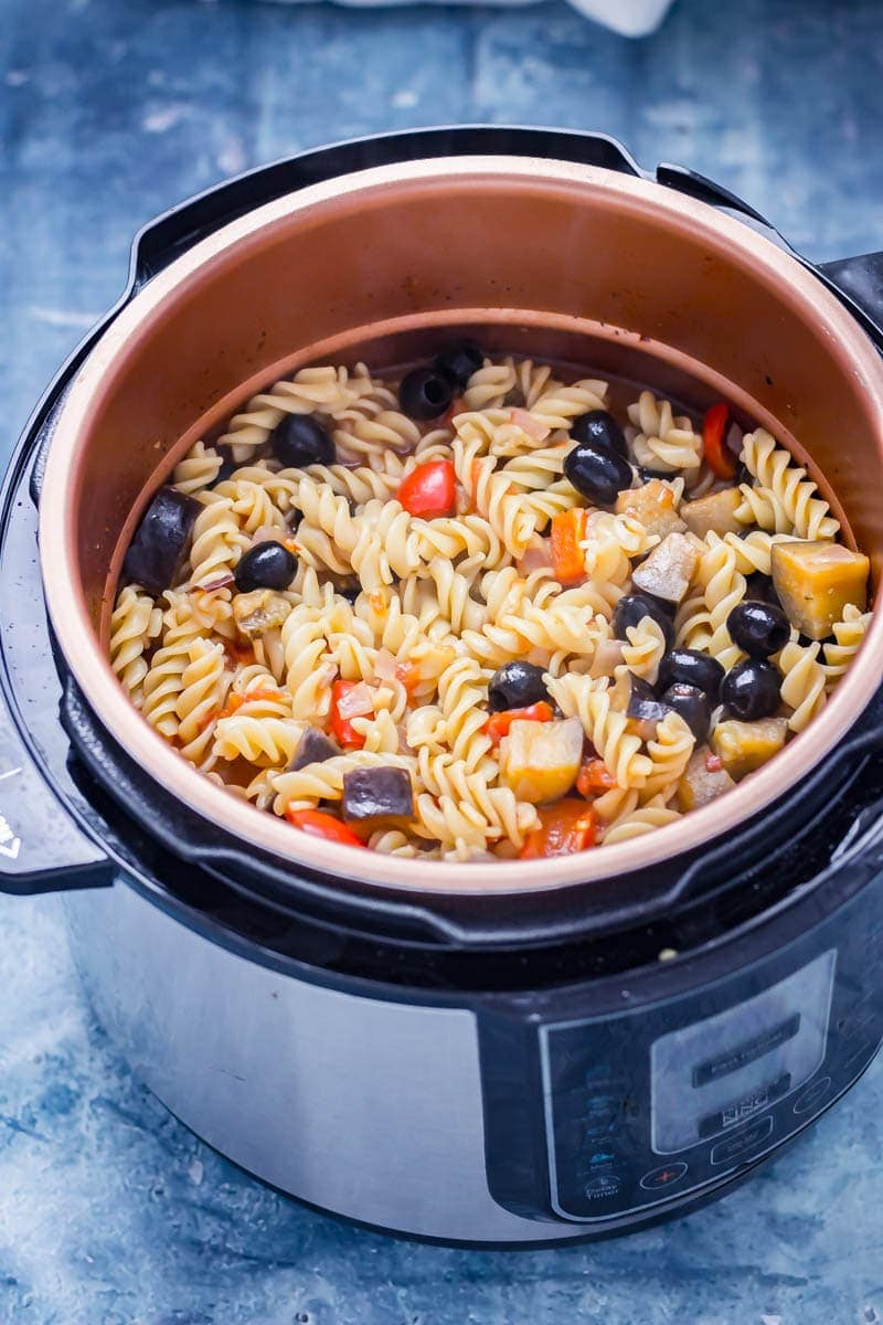 Pressure cooker pasta in a pressure cooker with olives, peppers, aubergine and red onion