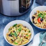 Two bowls of pasta with olives, pepper and aubergine sprinkled with parsley and pressure cooker in the background