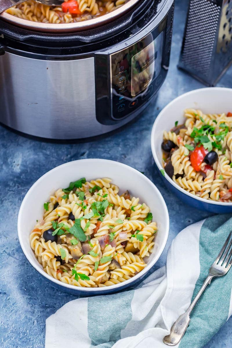 Two bowls of pressure cooker pasta with olives, pepper and aubergine sprinkled with parsley and pressure cooker in the background