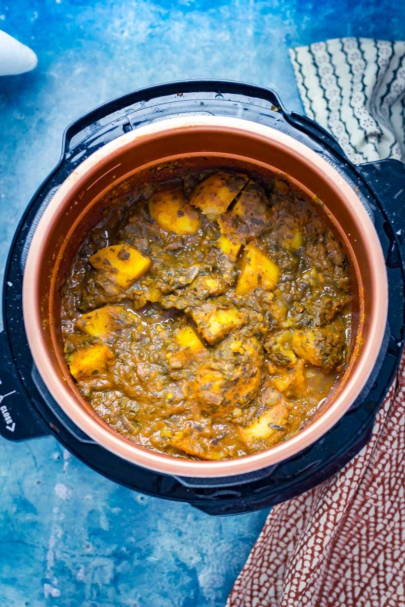 Saag aloo in a pressure cooker with a blue background