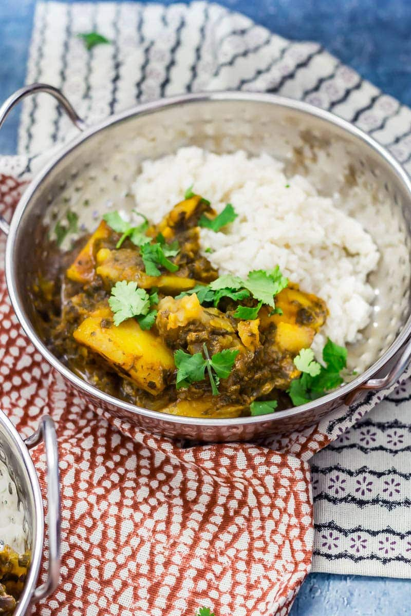 Metal bowl of saag aloo with rice, topped with coriander leaves on a patterned tea towel