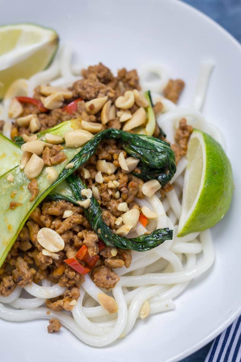 Close up of udon noodle stir fry with turkey mince, pak choi, chilli, peanuts and lime wedges on a white plate