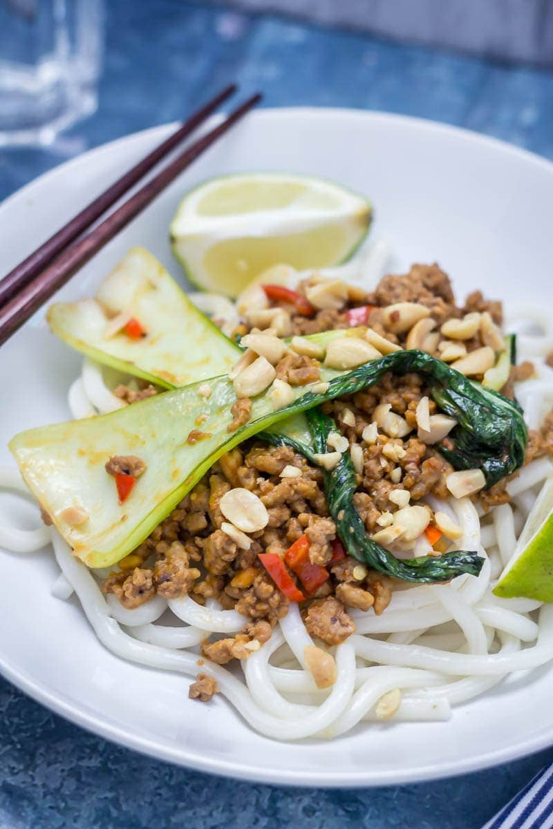 Udon noodle stir fry in a white bowl with turkey mince, pak choi and lime wedges with chopsticks in the background