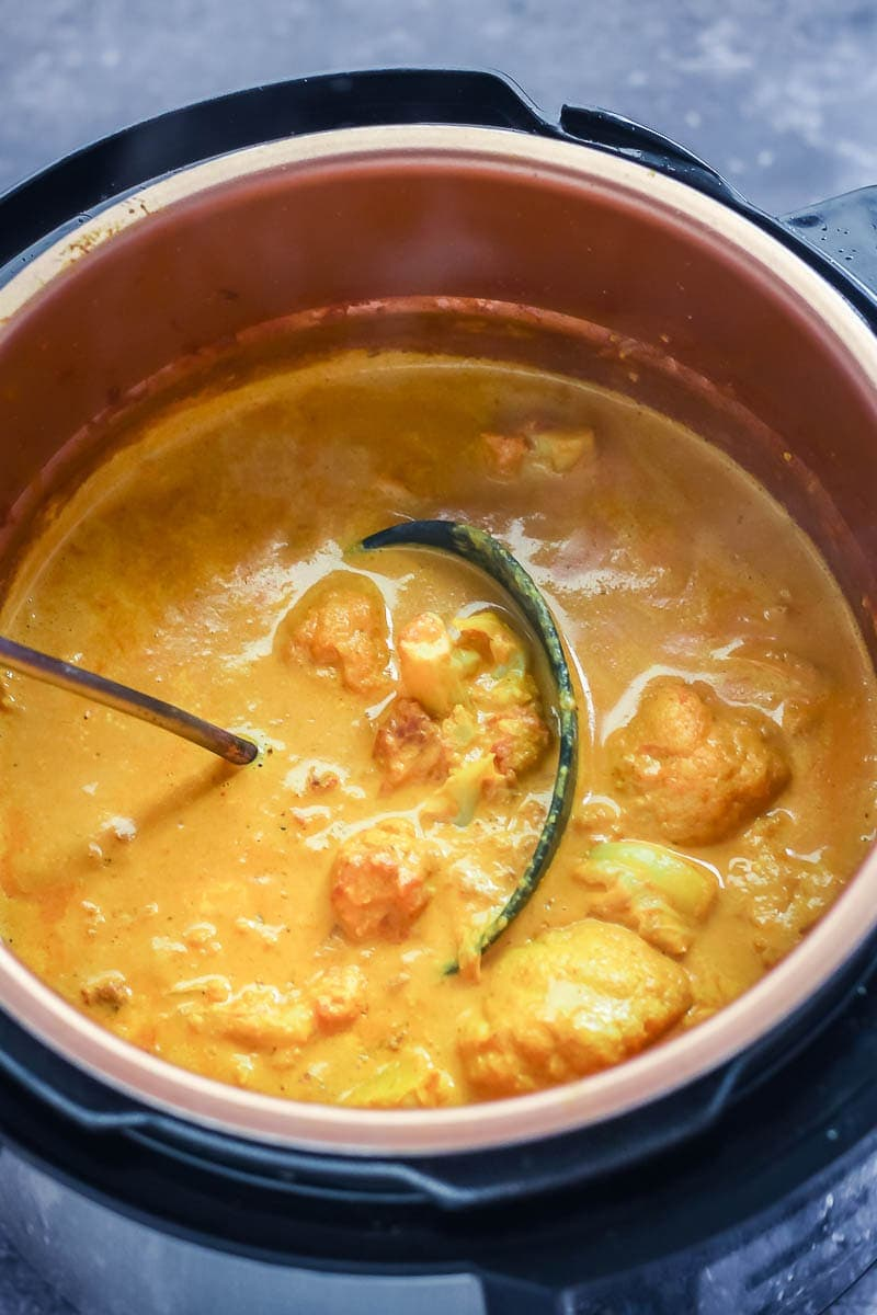 Creamy cauliflower curry in the pressure cooker with a ladle