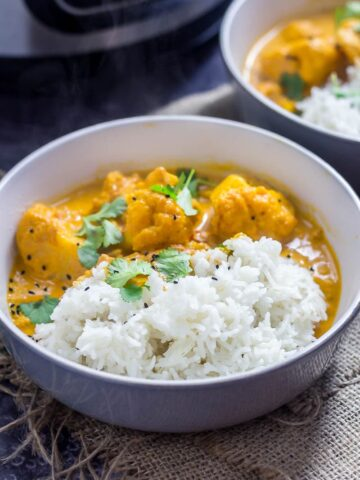 Bowl of creamy cauliflower curry with rice on a hesian mat