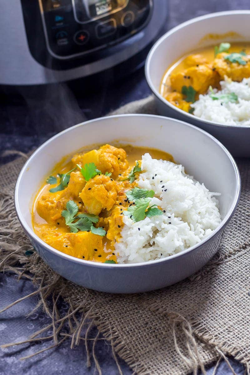 Two bowls of creamy cauliflower curry with the pressure cooker in the background