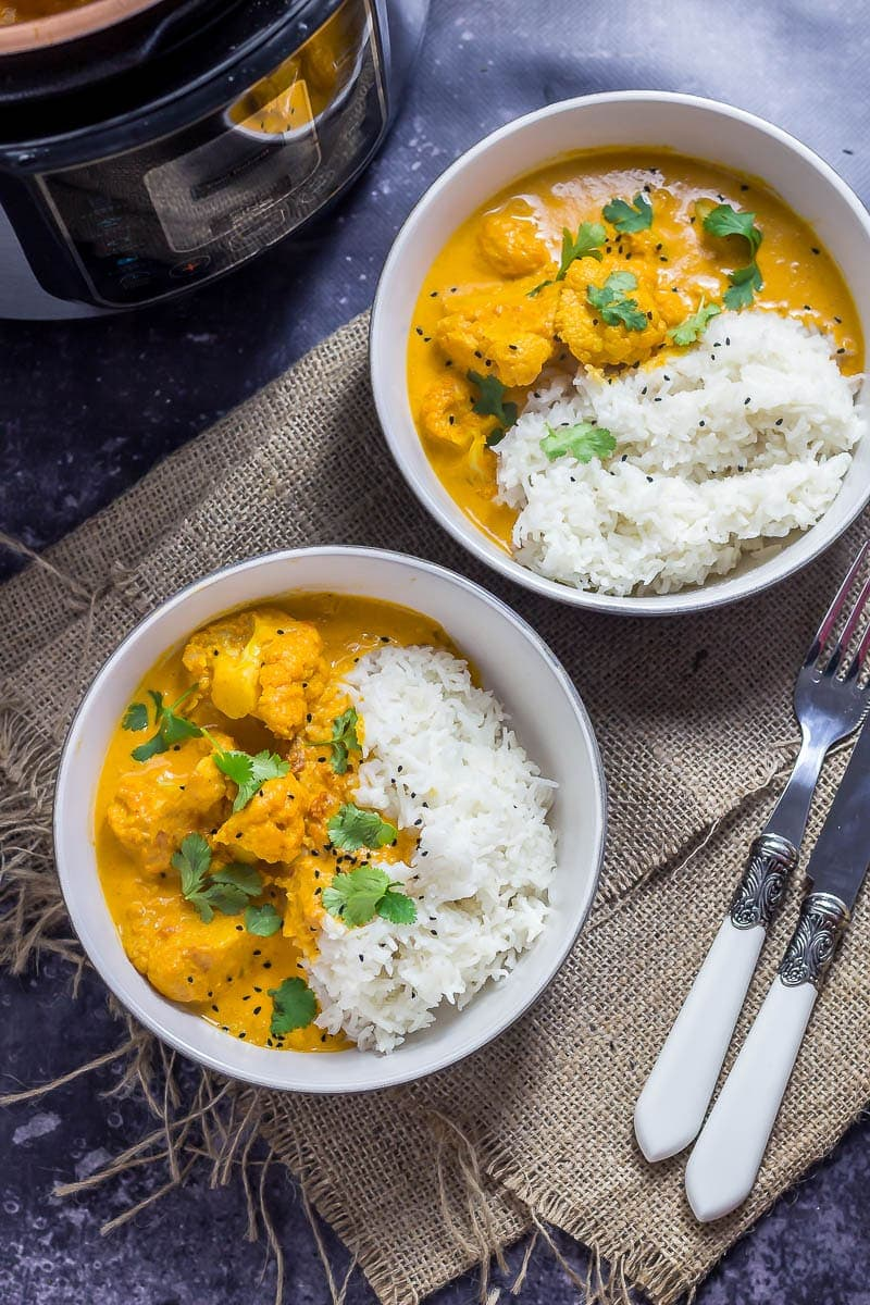 Creamy cauliflower curry in two bowls on hesian with a knife and fork and dark background