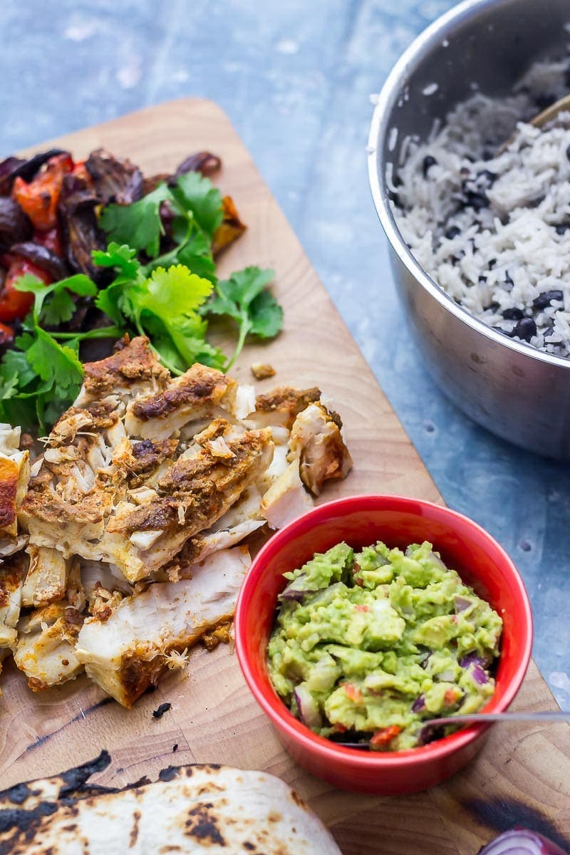 Fish, vegetables and guacamole on a wooden board