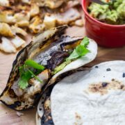 Fish tacos and tortillas on a wooden board
