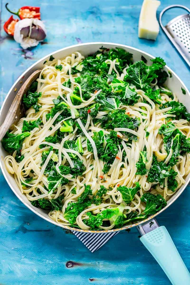 Frying pan of kale pasta with garlic, chilli and parmesan on a blue background