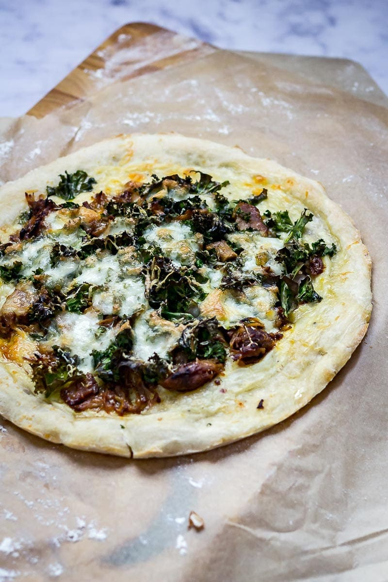 Leftover pulled pork pizza with kale on a piece of greaseproof paper and a wooden board