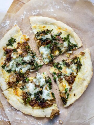 Leftover pulled pork pizza with kale sliced on a piece of greaseproof paper on a wooden board