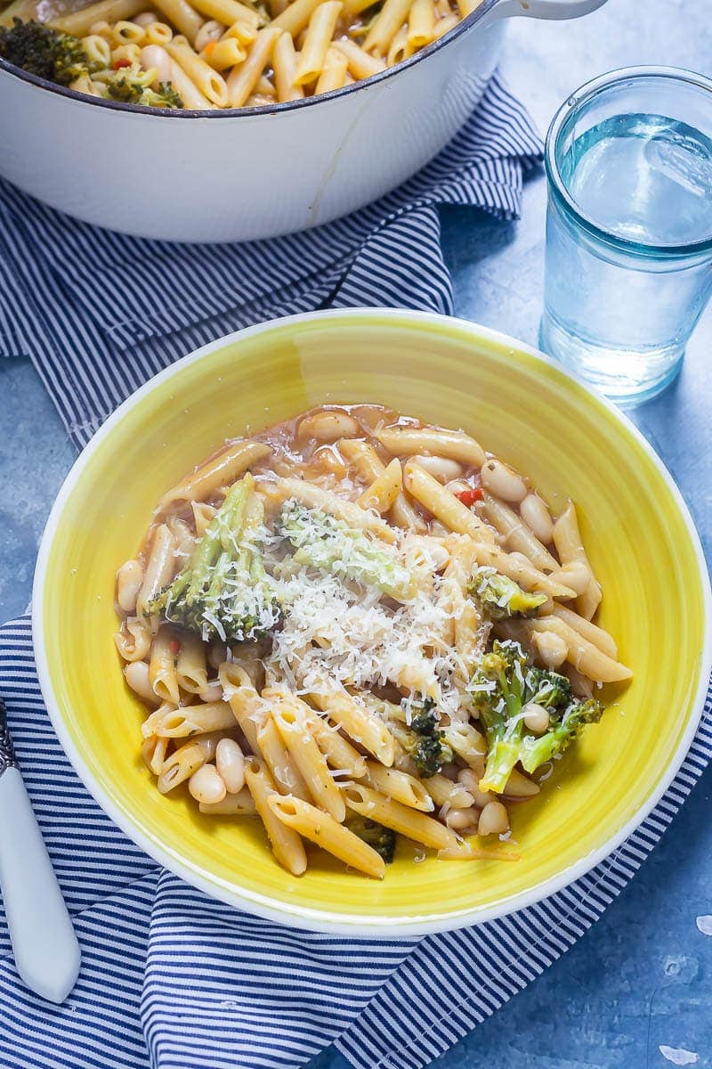 Yellow bowl of Broccoli and White Bean One Pot Pasta on a striped cloth with a glass of water