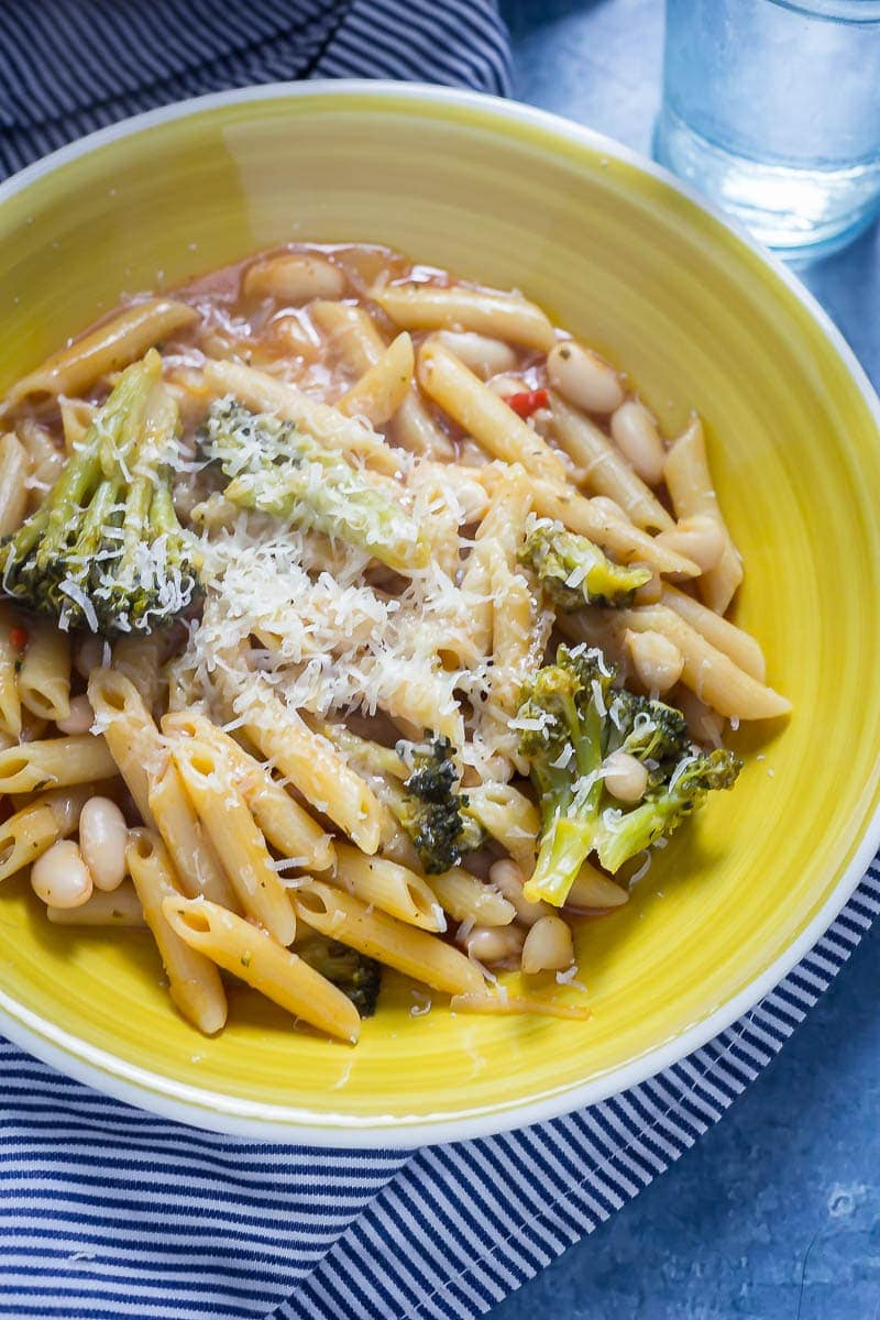 Broccoli and White Bean One Pot Pasta in a yellow bowl on a striped cloth