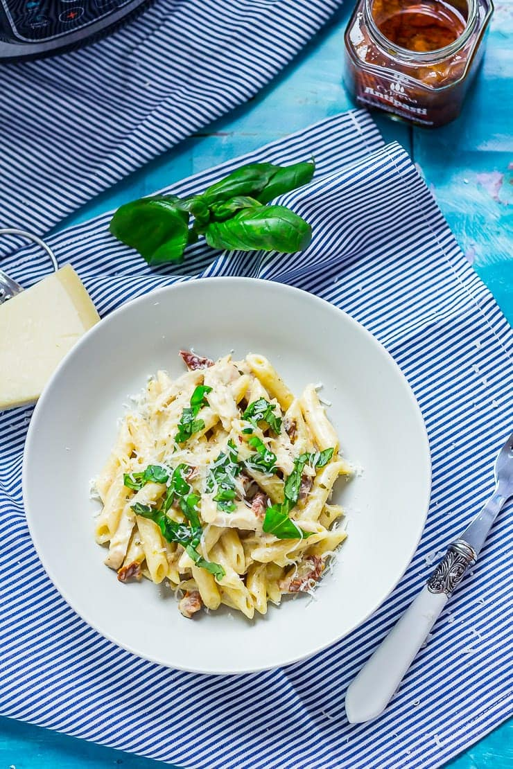 Overhead shot of pressure cooker pasta in a bowl on a striped cloth with a blue background