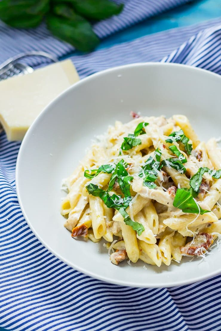 Bowl of creamy chicken pasta on a striped cloth with parmesan