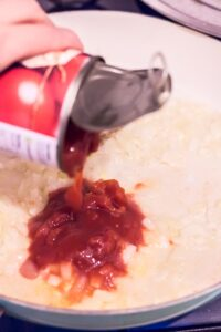 How to make pizza sauce. Pouring chopped tomatoes into a frying pan with onions