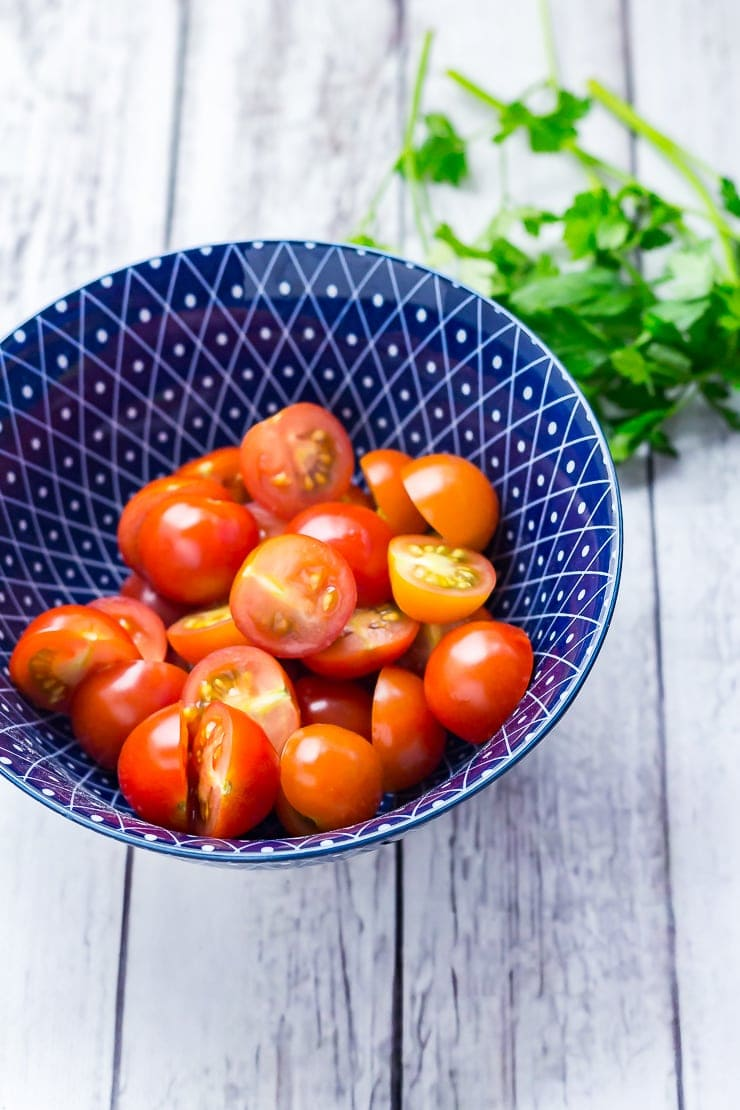 Blue bowl of halved cherry tomatoes on a distressed wooden background