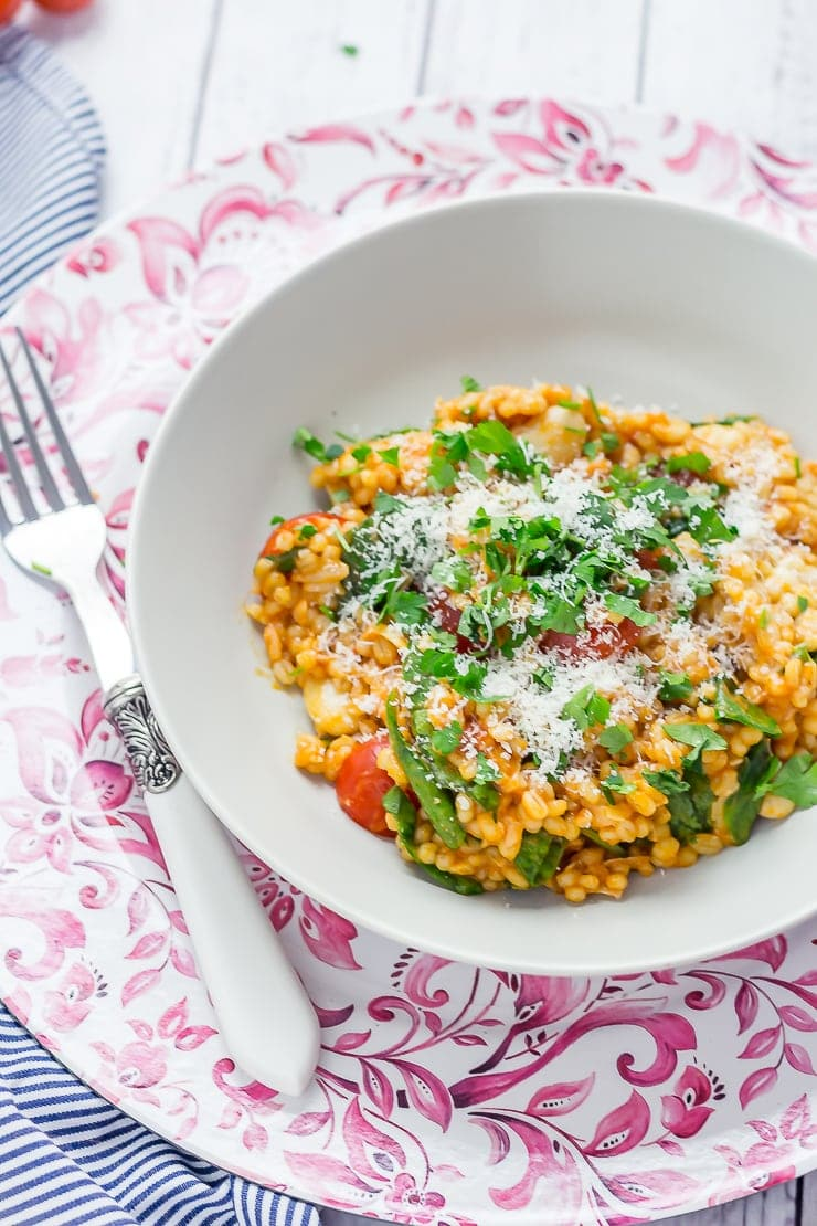 Bowl of One Pot Cheesy Pearl Barley with Tomatoes on a pink platter